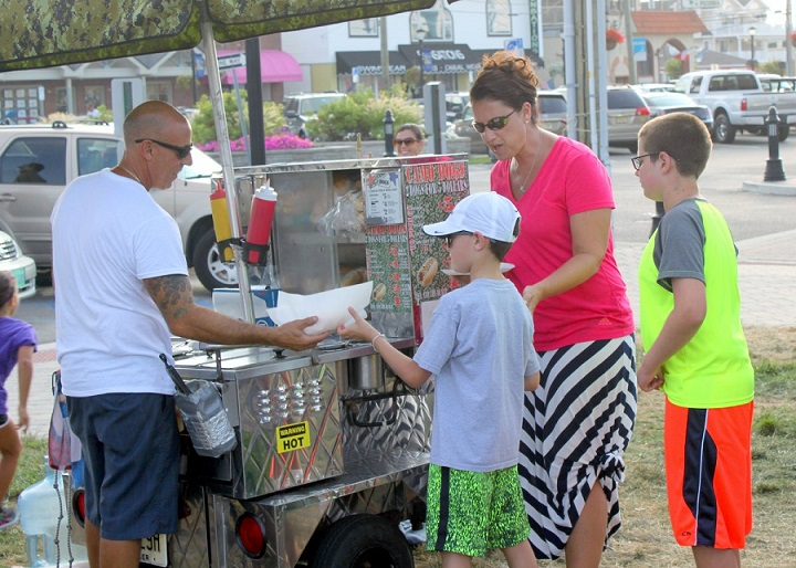 Families are invited to Excursion Park on August 2 for free entertainment, give-aways and activities during Sea Isle City's annual National Night Out celebration. Shown handing complementary food and snacks to guests in 2015 is Anthony DiAntonio, owner of Camo Dogs Hot Dogs.