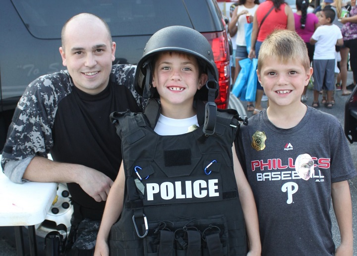 ) Kids will get an up-close look at a wide variety of police and safety equipment during National Night Out in Sea Isle City on August 2. Shown with SICPD Patrolman Matthew Mehlhouse in 2015 are brothers Bryce McManus, 8, and Gavin McManus, 7, of Oreland, PA.