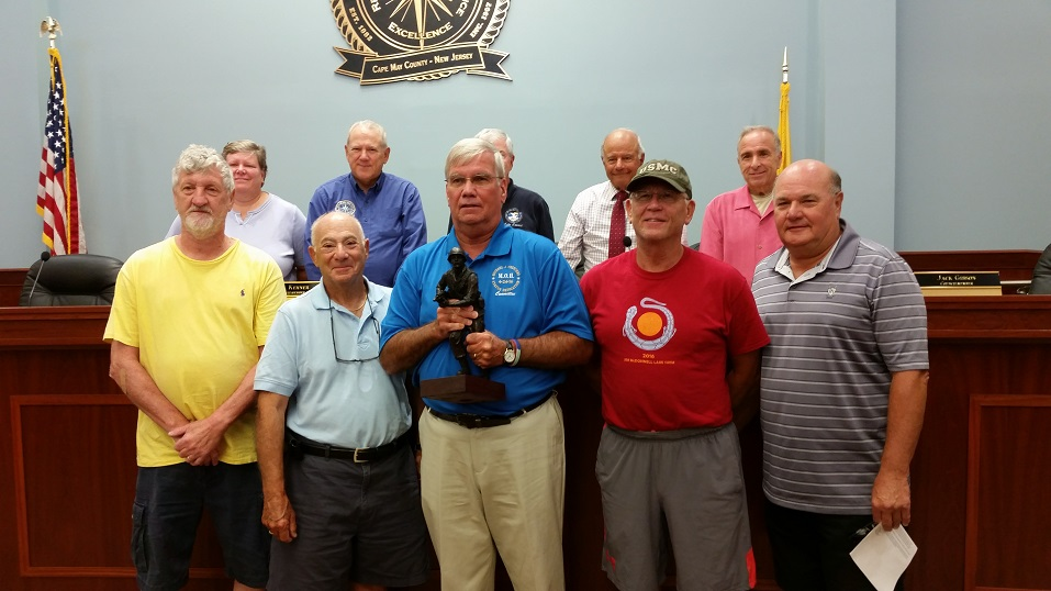 """Bill Crean, treasurer of the Cpl. Michael Crescenz Medal of Honor Committee, holds a miniature version of a statue of Crescenz, a Vietnam War hero who spent his summer vacations in Sea Isle City. Accompanied by veterans, Crean presented the """"modello"""" to city officials Tursday."""