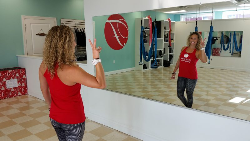 Cicitta gazes at herself in a large mirror in her workout studio.