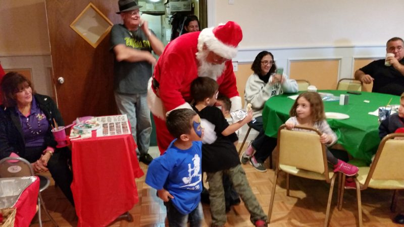 Santa greets and hugs some of the children who rushed up to see him.