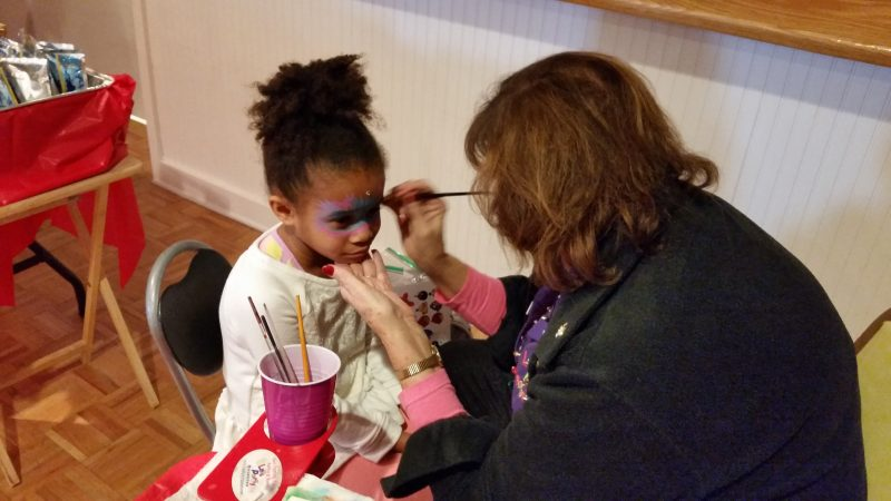 Aubrey McCatty, 6, of Dennis Township, has her face painted by Jinny Mulford of Let's Party Painters of Corbin City.