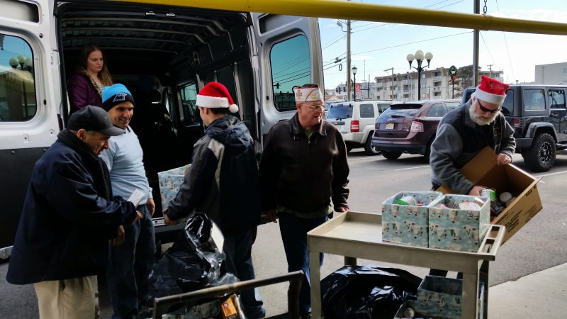 The mayor, left, is helped by local volunteers while loading toys and food into a van.