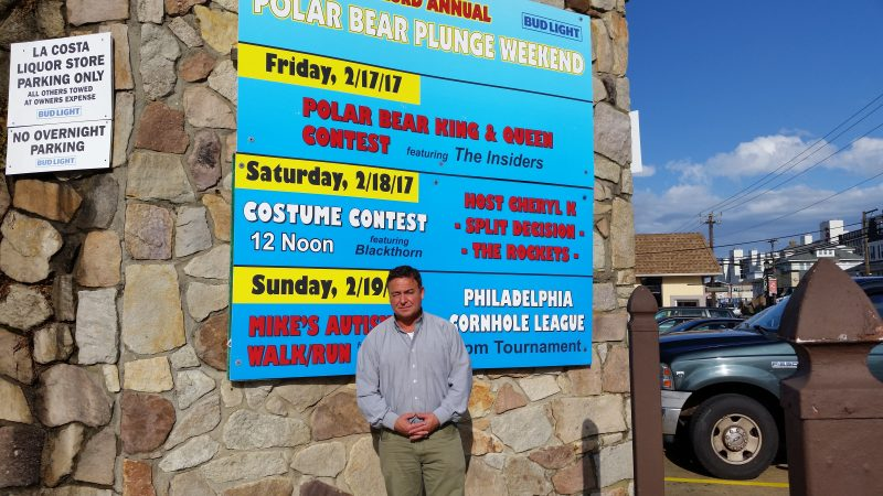 Bennett stands in front of a sign at LaCosta that advertises the array of Polar Bear events scheduled for the weekend of Feb. 17-19.