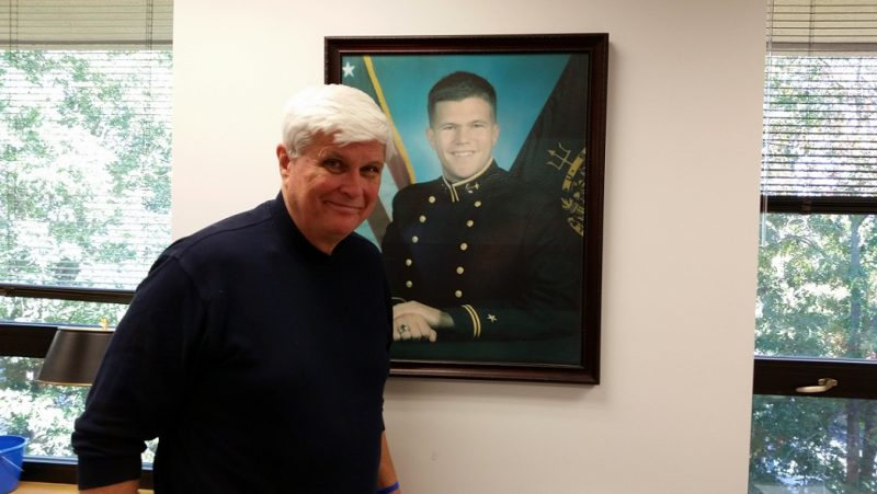 Bill Elliott stands in front of the Naval Academy portrait of his son that serves as the iconic image of the John R. Elliott HERO Campaign for Designated Drivers.