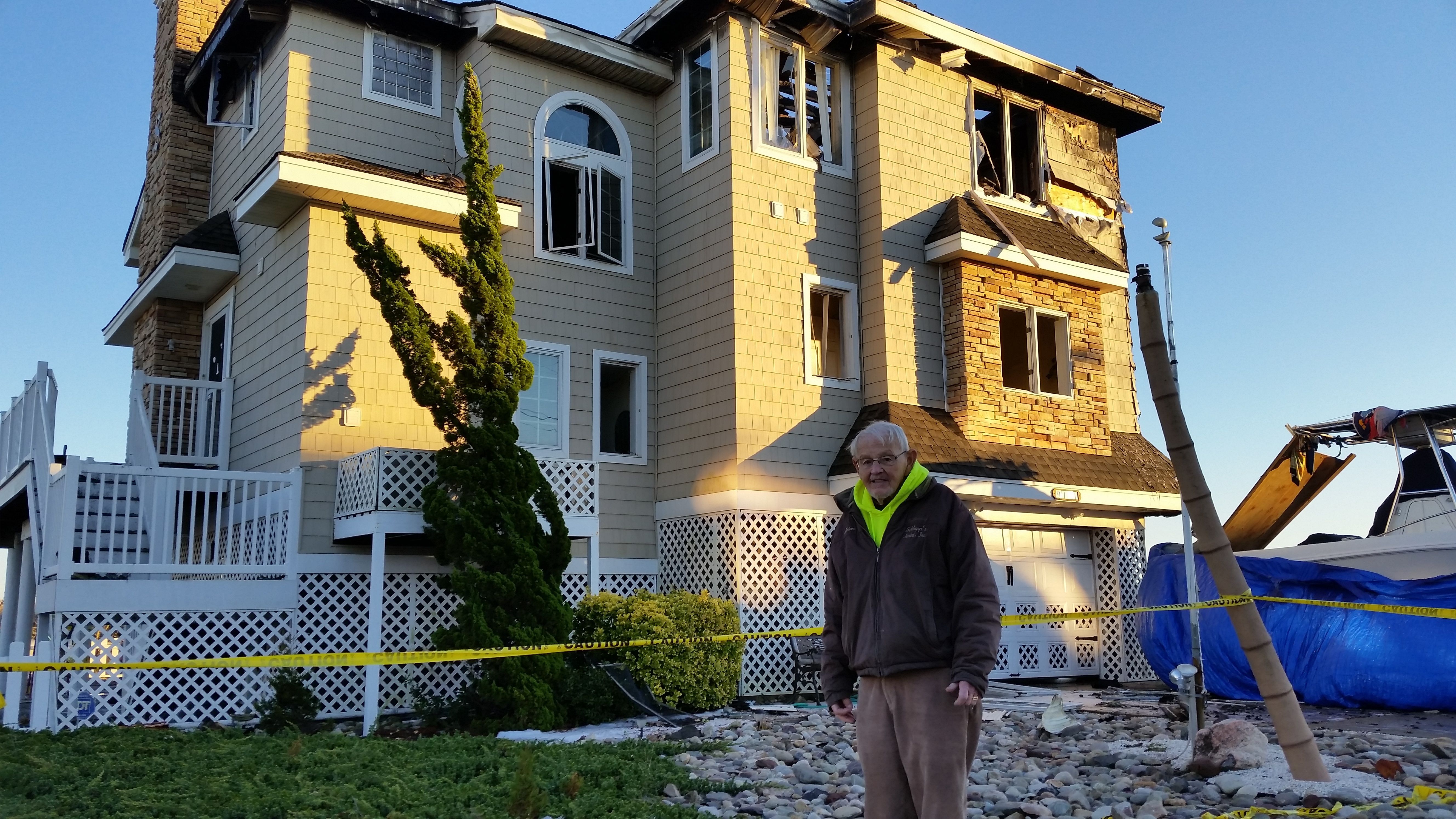 Ron Schlupp Stands In Front Of His Severely Damaged Home